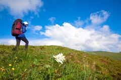 woman with tourist knapsack on mountain - stock photo