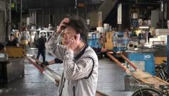 Fish trader holds a meeting over the phone at the Tsukiji market in Tokyo Stock Footage