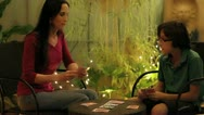 A mom and son playing card game in a soft lit patio outdoors - wide 2 shot Stock Footage