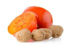 ripe persimmons and nuts - stock photo