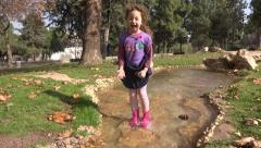 Little girl play in water streem Stock Footage