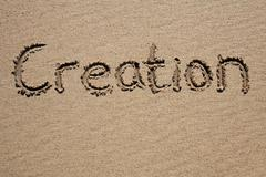 Creation, written on a sandy beach. Stock Photos