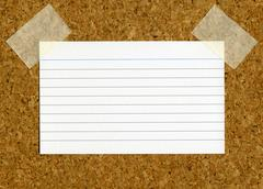 Blank index card stick to a cork notice board. Stock Photos