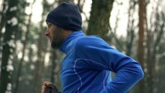 Lone runner in wintry wood, slow motion shot at 240fps Stock Footage