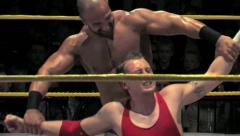WWE Pro Wrestling Superstar Daivari Applies Submission Hold to Opponent - stock footage