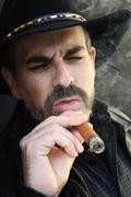 bearded man smoking cigar - stock photo