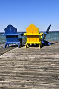 chairs on wooden dock at lake - stock photo