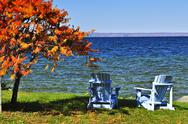 Stock Photo of wooden chairs on autumn lake