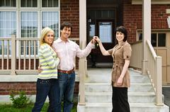 Happy couple with real estate agent Stock Photos