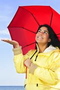 beautiful young woman in raincoat with umbrella checking for rain - stock photo