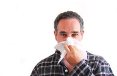 man with cold blowing nose - stock photo