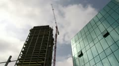Clouds passing by glass building / construction crane Stock Footage