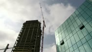Stock Video Footage of Clouds passing by glass building / construction crane