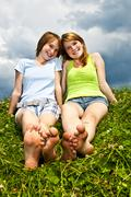 young girls sitting in meadow - stock photo