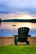 wooden chair at sunset on beach - stock photo
