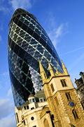 Gherkin building and church of st. andrew undershaft in london Stock Photos