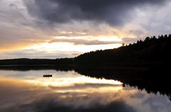 Lake sunset over forest Stock Photos