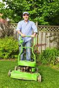 man mowing lawn - stock photo