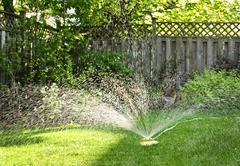 lawn sprinkler watering grass - stock photo