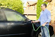 Stock Photo of man washing car on driveway