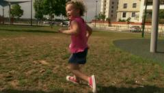 Little Caucasian Girl running at playground / park in slow motion Stock Footage