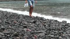 A guy walking in the gravel on the beach (return) Stock Footage