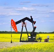 nodding oil pump in prairies - stock photo