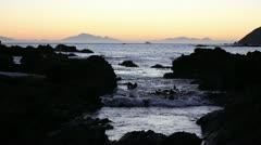 Sunset ocean, rocky coastline Stock Footage