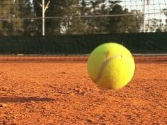 Tennis ball falling on a clay court. Slow Motion - stock footage