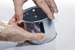 hands installing metal pot light fixture - stock photo