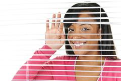 smiling woman looking through blinds - stock photo