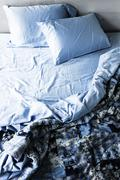Unmade bed and bedding Stock Photos
