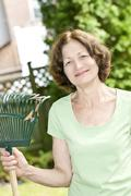 Stock Photo of senior woman holding rake