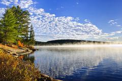 Autumn lake shore with fog Stock Photos