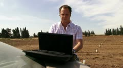 Guy working on the field with laptop. Typing. - stock footage