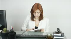 woman in the office, cut sheet of paper - stock footage
