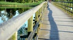 Wooden lake bridge railing closeup  couple walk in distance Stock Footage
