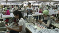 Garment Factory: Female garment workers with supervisor watching - stock footage