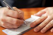 Man writing a check Stock Photos
