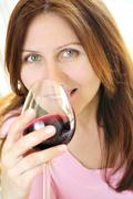 mature woman with a glass of red wine - stock photo