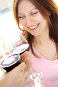 mature woman toasting with red wine - stock photo
