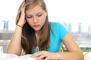 Stock Photo of teenage girl studying with textbooks
