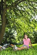 Teinityttö rentouttava puistossa hänen polkupyörän Kuvituskuvat