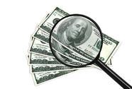 Dollars and magnifying Stock Photos