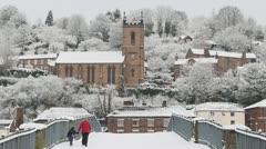 Walking across the snow covered Iron Bridge, Ironbridge, England. Stock Footage