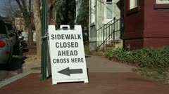 Sign notifying sidewalk ahead is closed Stock Footage