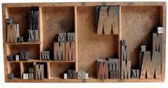 letterpress M in wood and metal in a case - stock photo