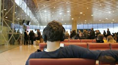 Man listens to music in a waiting lounge Stock Footage