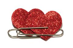 Two red hearts attached with a paper clip Stock Photos