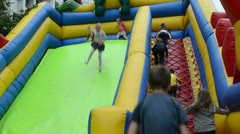 Children climb and slide on inflatable rubber castle playground Stock Footage